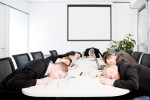 Executives asleep at a conference table