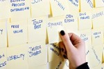 Hand reaching for a Sticky Note with a buzzword on a wall full of them.