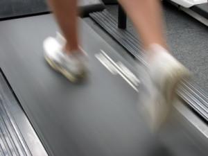 Closeup of running man using treadmill.