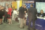 Handful of journalists standing near job fair booths at convention